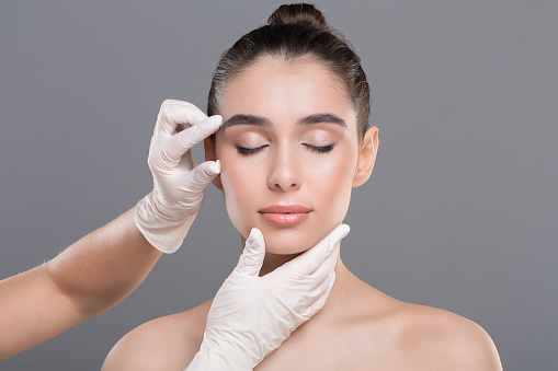 Youth and beauty treatment. Cosmetologist examining facial wrinkles on young woman face