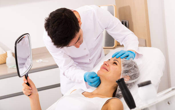 Cosmetologist giving consultation to woman patient stock photo