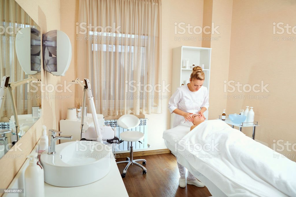 Cosmetologist is a professional with a patient in the office of stock photo
