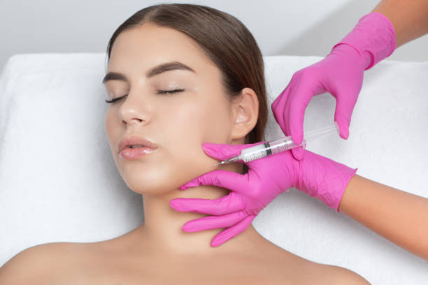 Cosmetologist makes lipolytic injections to burn fat on the chin, cheeks and neck of a woman against double chin. Female aesthetic cosmetology in a beauty salon.Cosmetology concept. stock photo