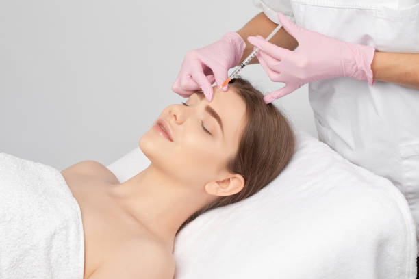 Cosmetologist makes rejuvenating anti wrinkle injections on the face of a beautiful woman. Female aesthetic cosmetology in a beauty salon. stock photo