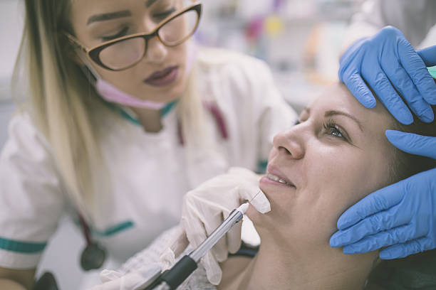 Cosmetologist making botox injection in female lips - Photo