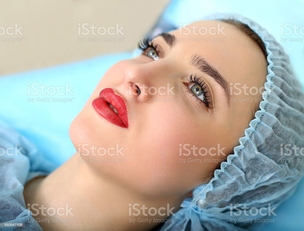 Cosmetologist making permanent makeup on woman's face stock photo