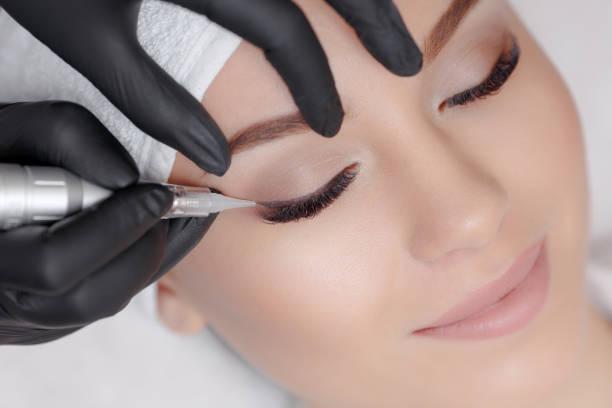 Cosmetologist making permanent makeup stock photo