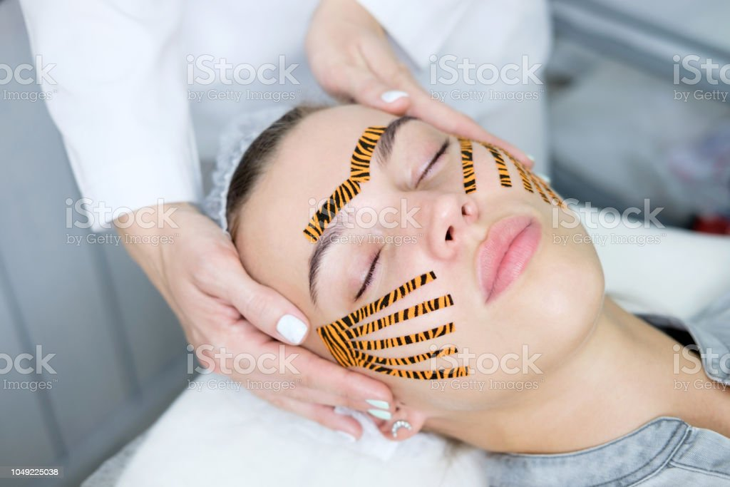 Cosmetologist Making Taping Face Procedure Using Tiger