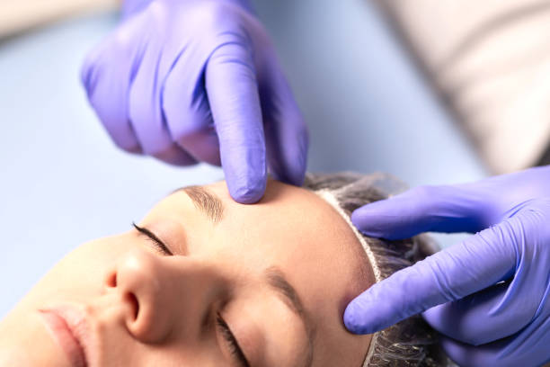 Cosmetologist, plastic surgeon or doctor with patient or customer. Consultation and plan before facial surgery in hospital, skin treatment or facelift in clinic. stock photo