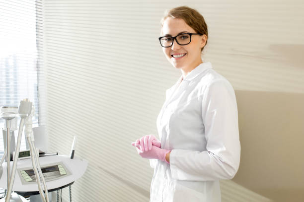Cosmetologist Posing in Office Waist up portrait of beautiful female cosmetologist smiling looking at camera and posing in sunlit modern SPA salon standing by wall, copy space beautician stock pictures, royalty-free photos & images