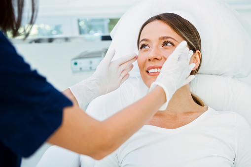 Cosmetologist preparing to doing cosmetic facial treatments for the young woman