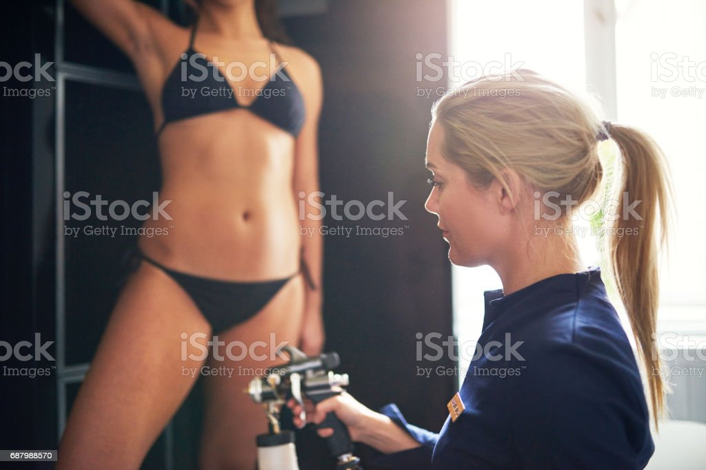 Cosmetologist spraying tan bodypaint on woman in salon stock photo