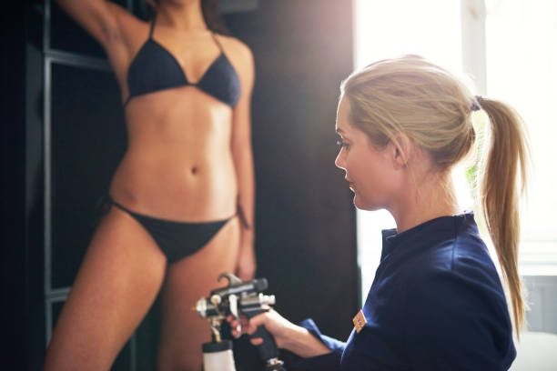 Cosmetologist spraying tan bodypaint on woman in salon Cosmetologist using aerograph for spray tan apply to young woman leg in beauty salon. airbrush stock pictures, royalty-free photos & images