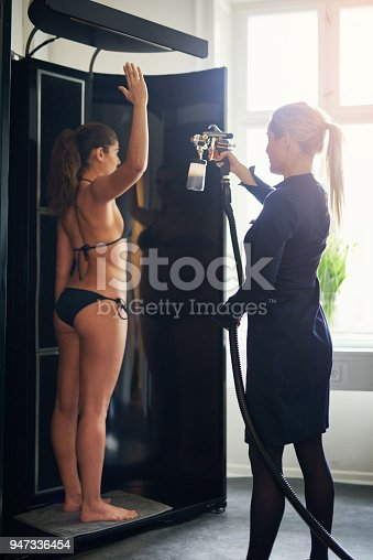 Beautician using airbrush for spray tan apply to young woman in beauty salon.
