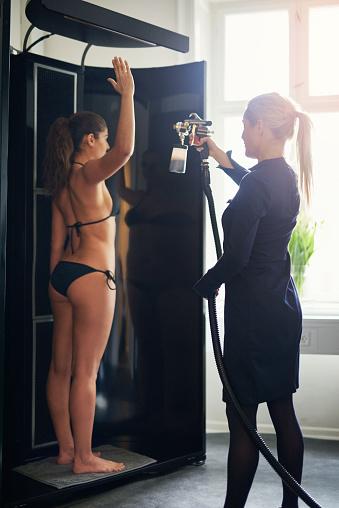 istock Cosmetologist spraying tan on woman in salon 947336454