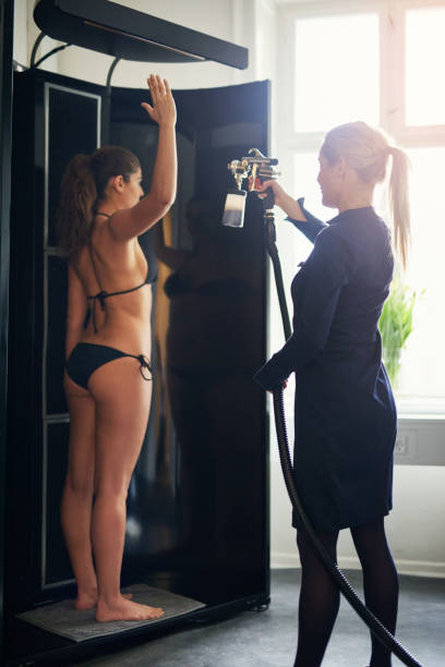 Cosmetologist spraying tan on woman in salon Beautician using airbrush for spray tan apply to young woman in beauty salon. airbrush stock pictures, royalty-free photos & images