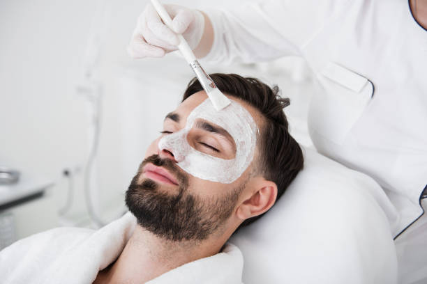 Cosmetologist using brush while putting white clay mask on male face stock photo