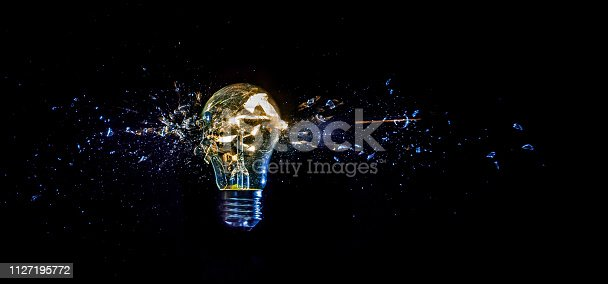 istock cosmic explosion of a burning light bulb with flying splinters and smoke on a black background with a flash 1127195772
