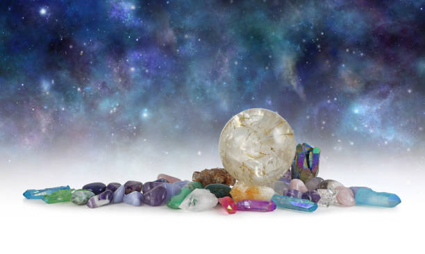 Cosmic Space Crystals Background Banner Huge rutilated Crystal Ball surrounded by tumbled healing stones and terminated quartz with space for copy above in celestial dark night sky crystal healing stock pictures, royalty-free photos & images