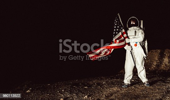 One man, astronaut exploring the land on the other planet alone at night, holding a USA national flag.