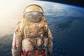 Cosmonaut or astronaut or spaceman in helmet at earth background view from outer space. Elements of this image furnished by NASA.