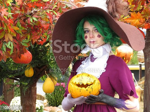 Moscow, Russia - October 2018: Girl cosplay character dressed as a witch stands with pumpkin in hands on autumn decorations background during festival Golden Autumn. Halloween concept, Jack o'Lantern