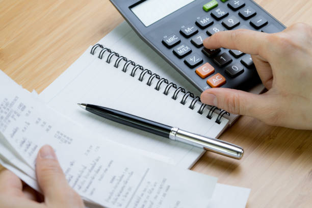 Cost calculation or bill payment concept, hand put finger on calculator and black pen on paper notepad with pile of bills in the left hand on wooden table stock photo