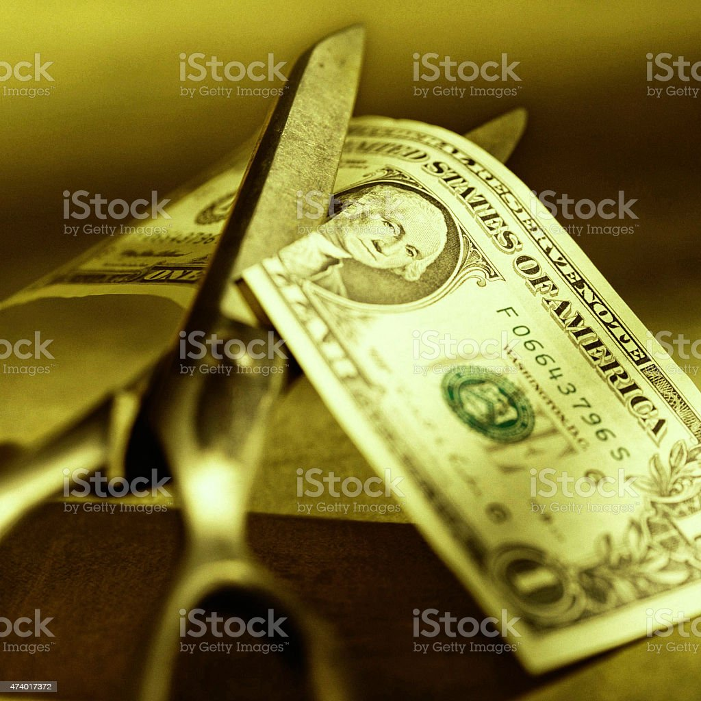 Cost Cutting with Sissors and US Dollar stock photo