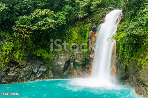 This is a horizontal, royalty free stock photograph of scenic Costa Rica, a Central American travel destination. The Rio Celeste waterfall is a natural landmark for eco tourists visiting Tenorio National Park. The flowing water falls over a rocky cliff, through green rainforest vegetation, and pools into an aqua color at the base. Photographed with a Nikon D800 DSLR camera.