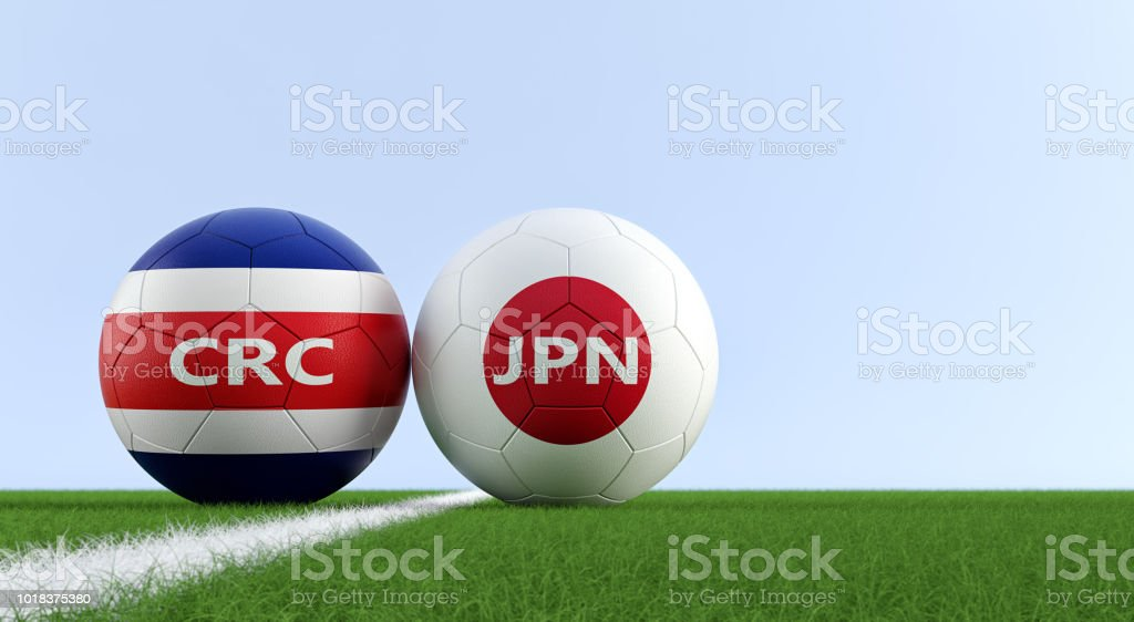 Costa Rica vs. Japan Soccer Match - Soccer balls in Costa Rica and Japan national colors on a soccer field. Copy space on the right side - 3D Rendering stock photo