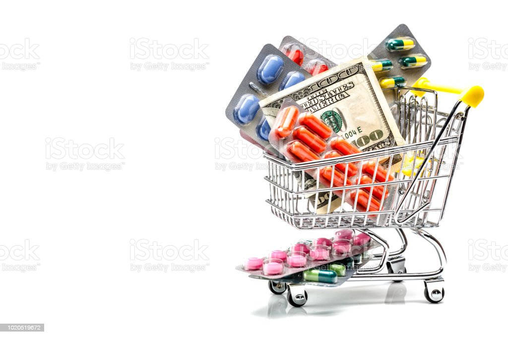 Costs of medicine. Blisters with pills and capsules in a shopping cart with dollar bill on white background. stock photo