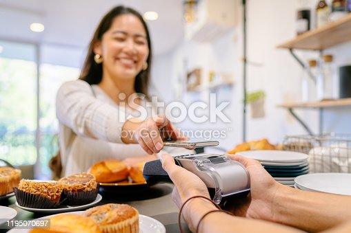 A female costumer is making a contactless payment in a cafe.