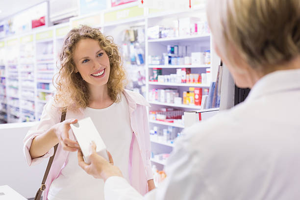costumer taking medicine box - chemist stock photos and pictures