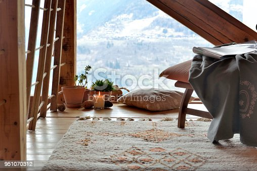 break room with chair, plants and candle in front of paned glass in a cottage of mountain
