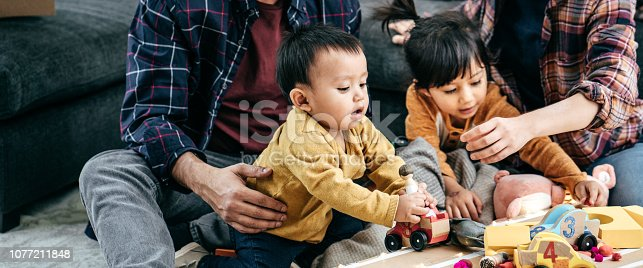 1082195070 istock photo Cosy family evening with kids and parents 1077211848