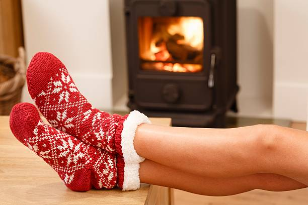 Cosy fire Womans feet in red Christmas socks by cozy wood burner alongside stock pictures, royalty-free photos & images