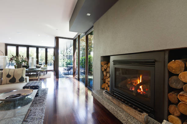 cosy gas log fire in architect designed modern luxury open plan home - warm house stock photos and pictures