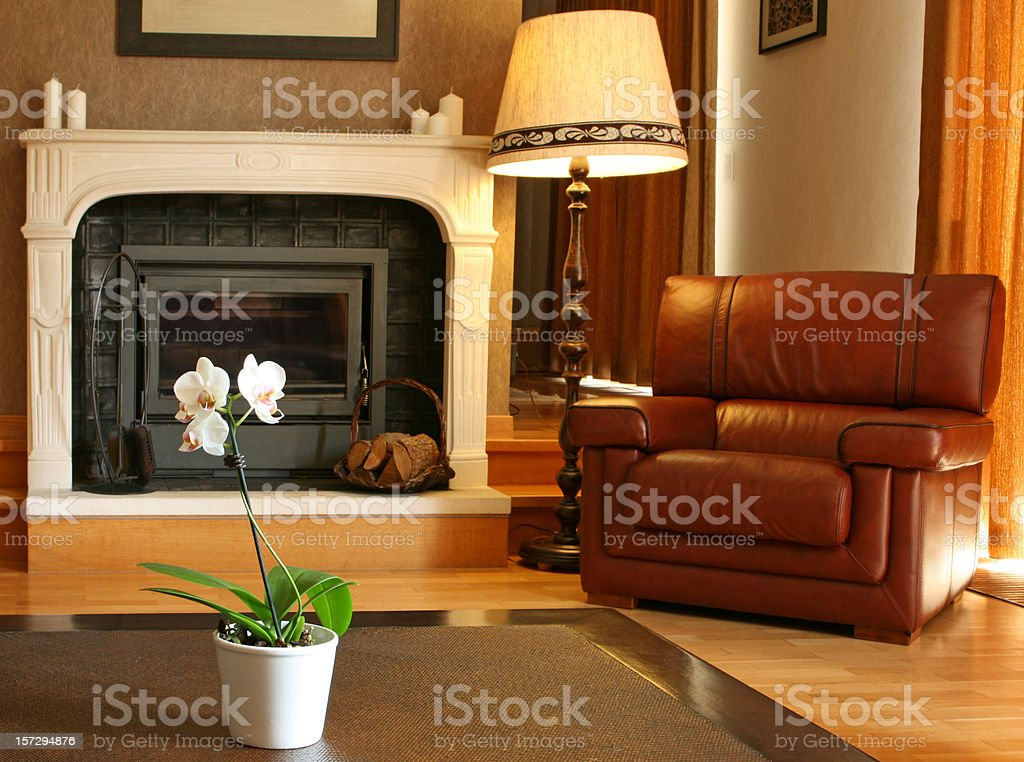 Cosy Home Interior: a Living Room with Fireplace and Armchair royalty-free stock photo