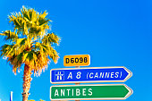 Cote d Azur road sign to Antibes and Cannes, palm and blue sky background, French riviera