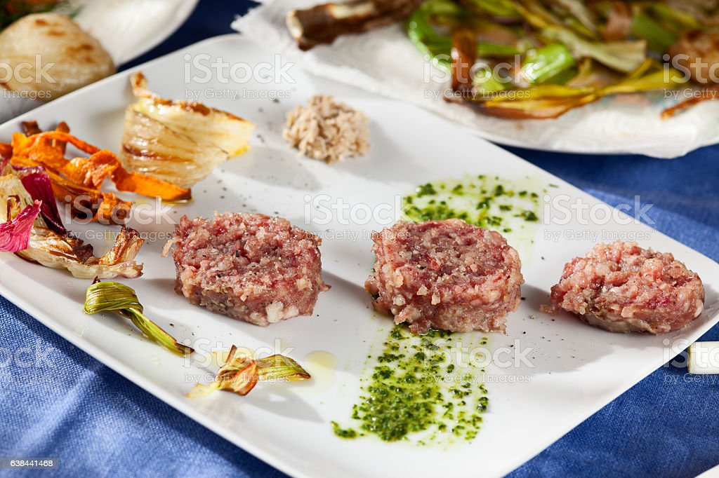 Cotechino with fried vegetables and sauces (horseradish, green sauce) stock photo