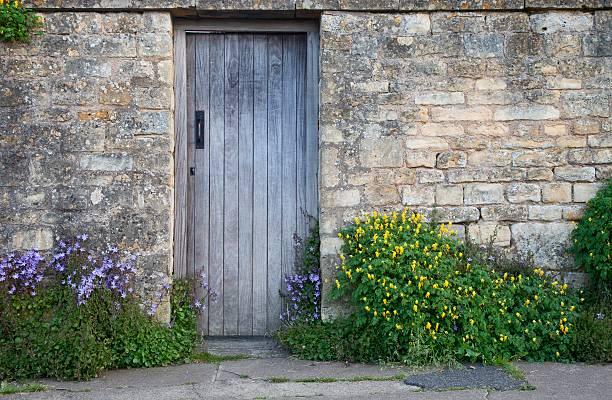 cotswold-wand mit hölzerne tür - steine für gartenmauer stock-fotos und bilder