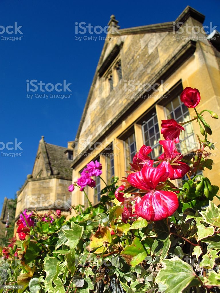 Cotswolds England Broadway village ivy and flowers fronting stone cottage stock photo
