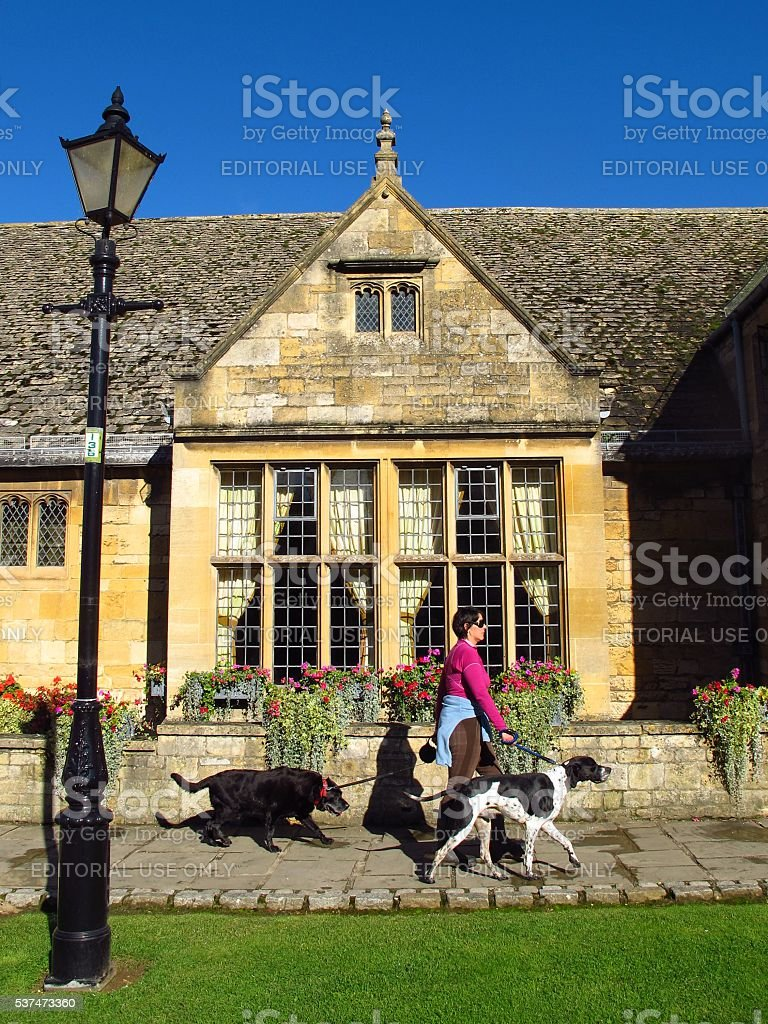 Cotswolds England Broadway village woman walking dogs stock photo