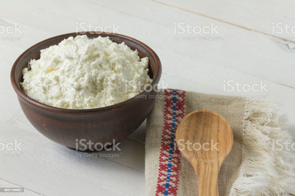 Cottage cheese in a brown ceramic bowl with authentic flax embroidered napkin and a wooden spoon on a white wooden background.  Close-up. royalty-free stock photo
