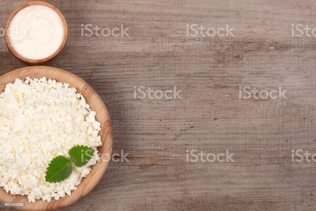 Cottage cheese in a wooden bowl with sour cream on old wooden background with copy space for your text. Top view stock photo
