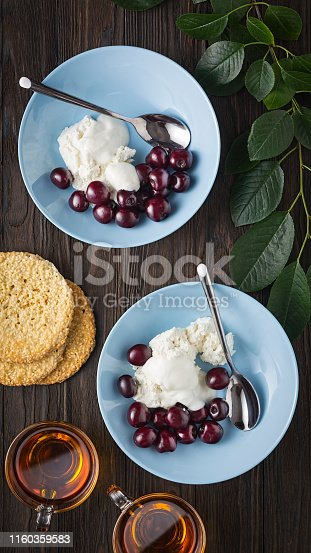 Healthy breakfast. Cottage cheese with delicate sour cream and ripe sweet cherries in blue bowls on a wooden table. View overhead.