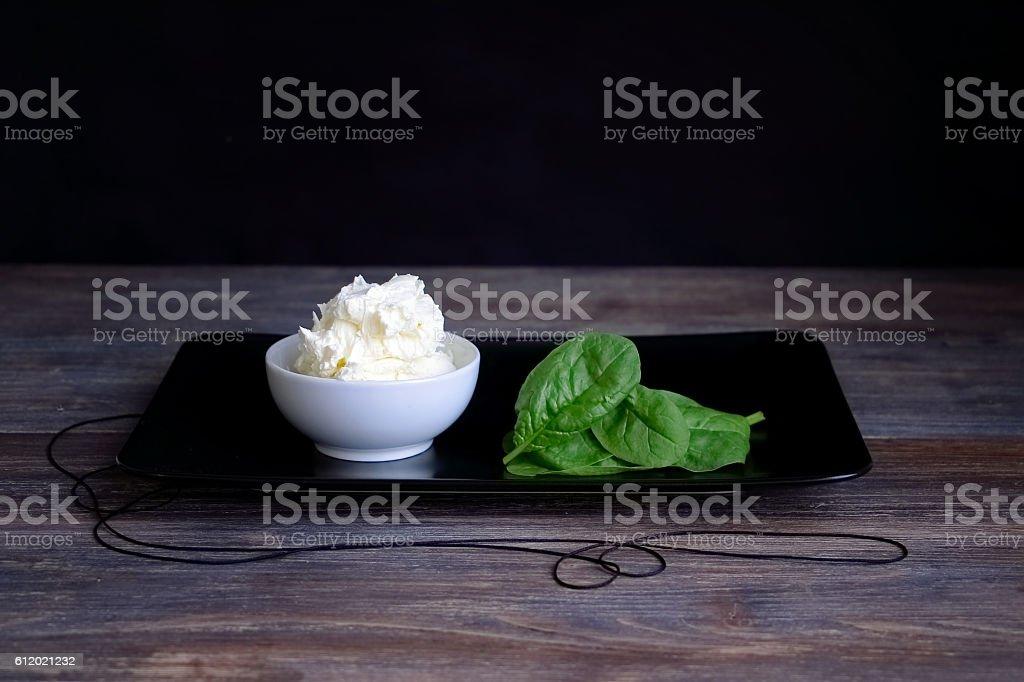 Cottage cheese, mascarpone in porcelain bowl against black background stock photo