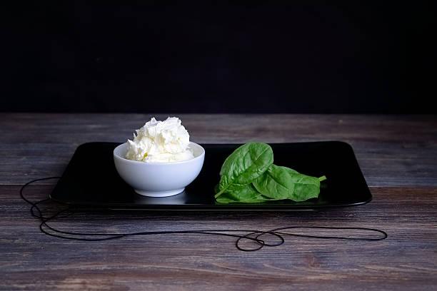 cottage cheese, mascarpone in porcelain bowl against black background - ricotta stock-fotos und bilder