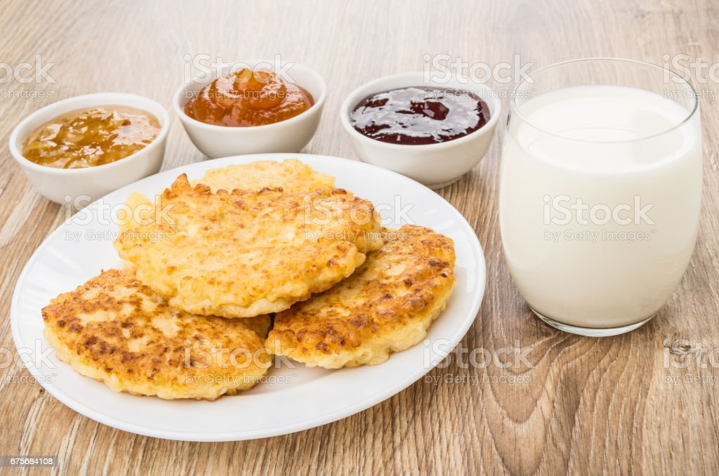 Cottage cheese pancake in plate, bowls with jam  and milk royalty-free stock photo