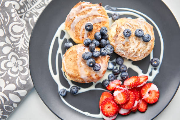 Cottage cheese pancakes or syrniki with blueberry and strawberries on black plate, closeup view. Condensed milk sauce. Russian, Ukrainian cuisine. Healthy tasty breakfast stock photo