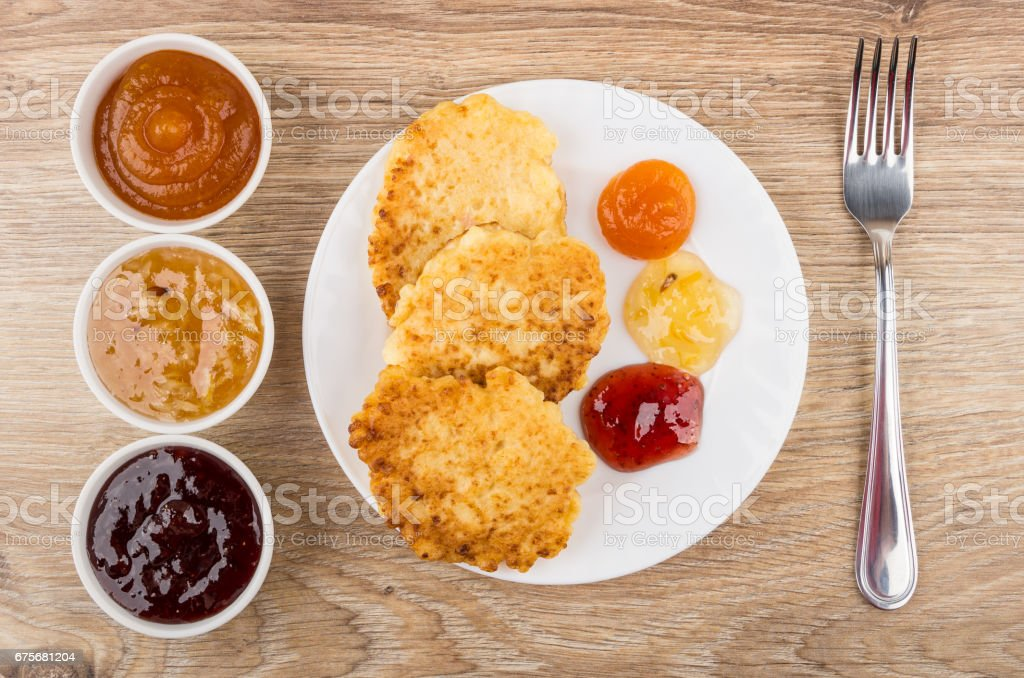 Cottage cheese pancakes with jam in plate, bowl with jam royalty-free stock photo
