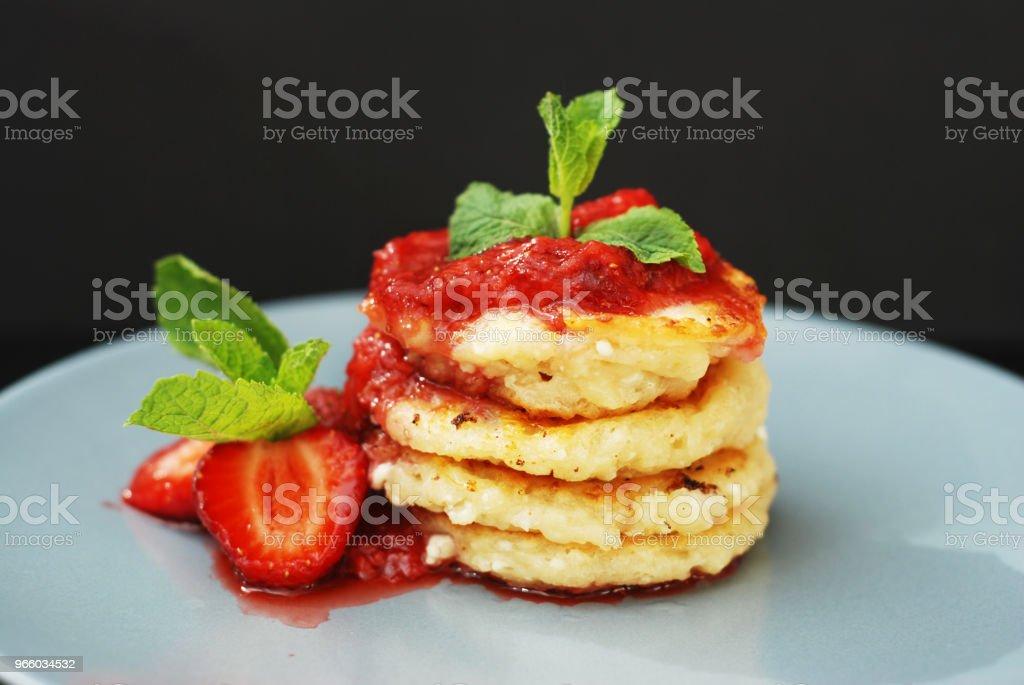 Quark-Pfannkuchen mit Erdbeeren und Strawberry Jam, Minze Blätter. Süßes Frühstück. Schwarzer Hintergrund. - Lizenzfrei Beere - Pflanzenbestandteile Stock-Foto