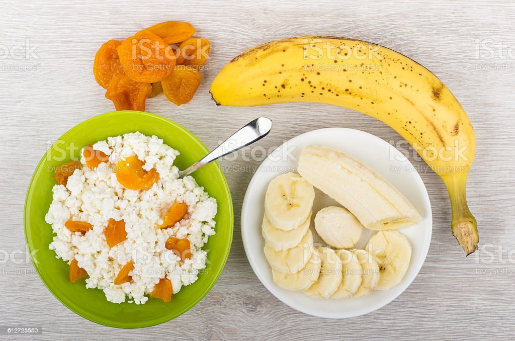 Cottage cheese with dried apricots in bowl and bananas stock photo